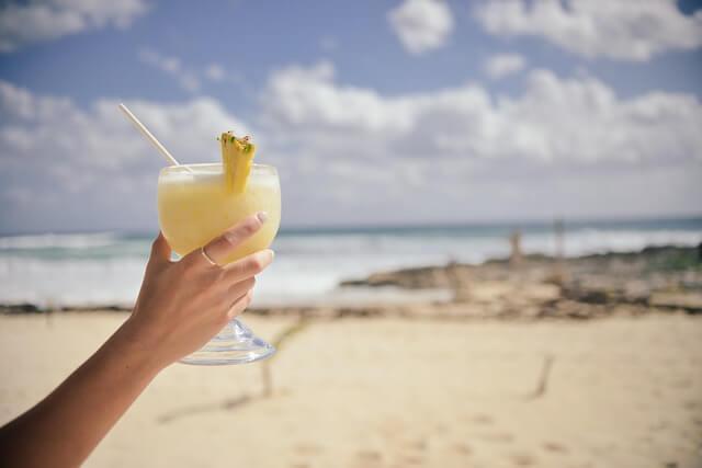 Drink dla kobiety Pina Colada na tle morza