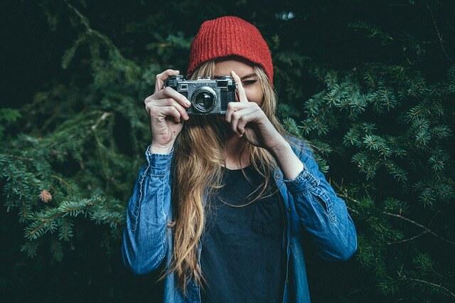 Dziewczyna hipster robiąca zdjęcia starym aparatem
