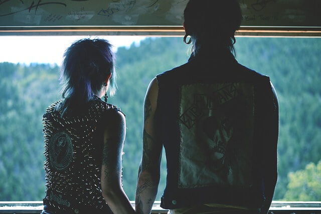 Para stojąca tyłem ubrana w stylu emo