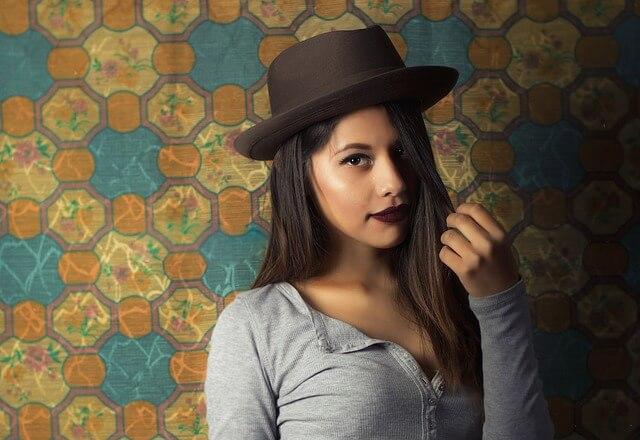 Ładna dziewczyna w kapeluszu bawi się włosami
