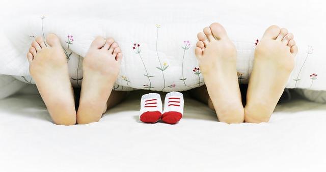 Stopy kobiety i mężczyzny leżących w łóżku i starających się o ciążę
