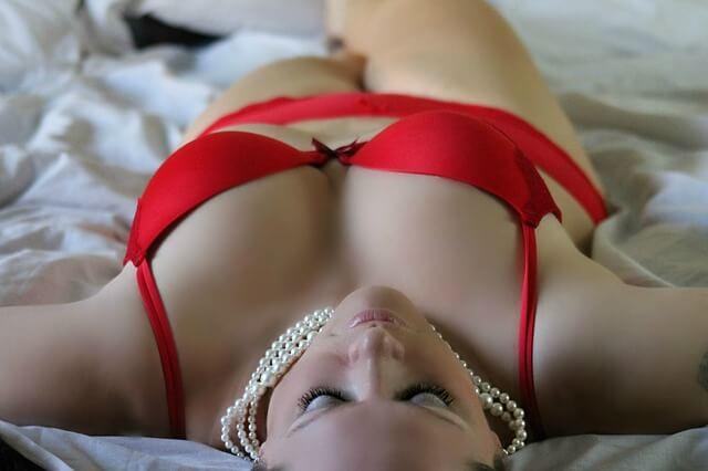 Kobieta z dużym biustem w kuszącym, czerwonym biustonoszu