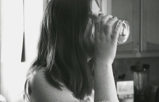 Kobieta pijąca wodę ze szklanki