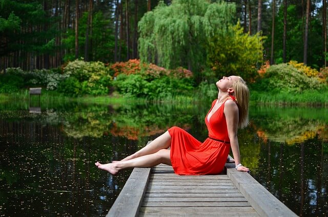 Niestresująca się kobieta leżąca na molo nad wodą