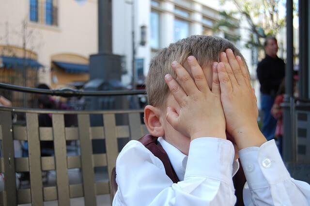 Mały chłopiec zakrywający twarz rękami