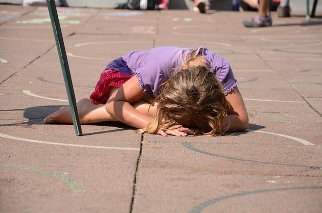 Mała dziewczynka leży na środku ulicy