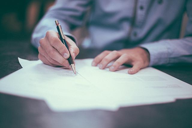 męzczyzna podpisujacy dokumenty